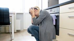 Junge deprimierte Frau, die auf Boden an der Küche sitzt Stockbilder