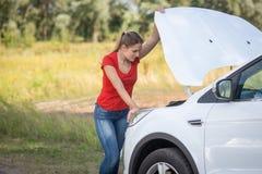 Junge deprimierte Frau, die auf der Maschine des defekten Autos auf dem Gebiet schaut Stockfotografie