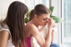 Junge deprimierte junge Frau, die, Freundin stützt ihre wi schreit Stockfotografie