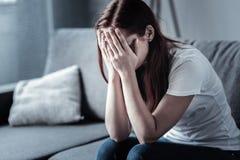 Junge deprimierte Frau, die ihr Gesicht versteckt Stockbild