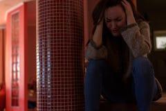 Junge deprimierte Frau, die zu Hause auf Schritten und dem Schreien sitzt Lizenzfreie Stockfotografie