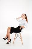 Junge deprimierte Geschäftsfrau, die Kopfschmerzen hat und auf dem Stuhl sitzt Lizenzfreies Stockbild