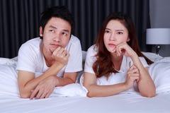 Junge deprimierte Paare auf Bett im Schlafzimmer Lizenzfreies Stockfoto