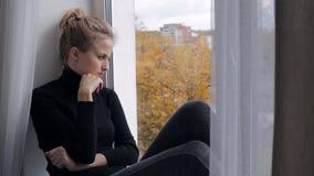 Junge deprimierte und traurige Frau, die auf dem Fensterbrett sitzt stock footage
