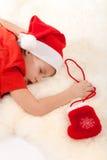 Junge, der über Geschenke schläft und träumt Lizenzfreies Stockfoto