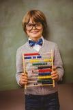 Junge, der Abakus vor Tafel hält Stockbilder