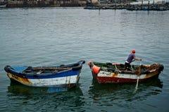 Junge, der Abfall im Hafen sammelt stockbild