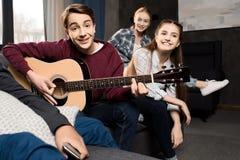 Junge, der acustic Gitarre während seine Freunde zu Hause hören spielt Stockfotos