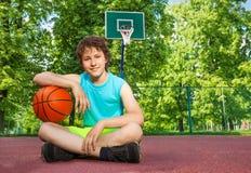 Junge, der allein mit Ellbogen auf dem Ball sitzt Stockbilder