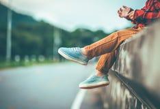 Junge, der allein mit ihren Füßen zeigen unten in Weinleseton sitzt stockbilder