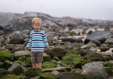 Junge, der allein unter Felsen steht Lizenzfreie Stockfotos