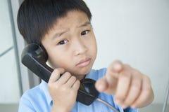 Junge, der allgemeines Telefon verwendet Stockfotos