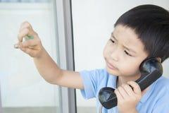 Junge, der allgemeines Telefon verwendet Lizenzfreies Stockfoto