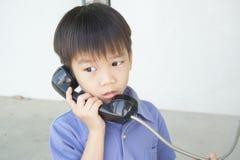 Junge, der allgemeines Telefon verwendet Stockfotografie