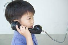 Junge, der allgemeines Telefon verwendet Stockbilder