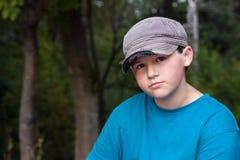 Junge, der alte Kappe und T-Shirt mit Forest Background trägt Stockfoto