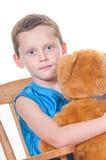 Junge, der angefüllten Bären umarmt Lizenzfreies Stockfoto