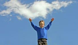 Junge, der Arme im Himmel hält Stockfoto
