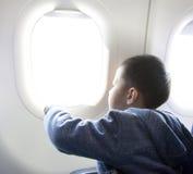Junge, der außerhalb des Flugzeugfensters schaut Lizenzfreies Stockfoto