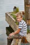 Junge, der auf altem hölzernem Pier sitzt Lizenzfreie Stockfotos