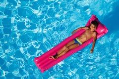 Junge, der auf aufblasbarem Aufenthaltsraum im Pool ein Sonnenbad nimmt lizenzfreies stockbild
