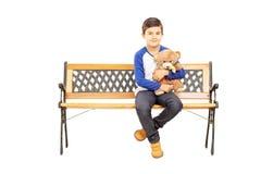 Junge, der auf Bank sitzt und Teddybären hält Lizenzfreies Stockbild