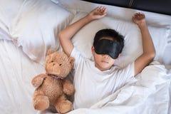 Junge, der auf Bett mit weißem Kissen und den Blättern des Teddybären tragen Schlafmaske schläft Lizenzfreie Stockfotos