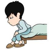 Junge, der auf Bett sitzt Stockfotos