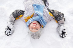Junge, der auf Boden bildenschnee-Engel legt Lizenzfreie Stockbilder