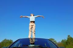 Junge, der auf Dach des Autos, öffnende Hände steht stockfotos