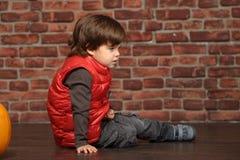 Junge, der auf dem Boden sitzt stockbild