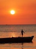 Junge, der auf dem Boot silhouettiert gegen einen Leuchtorangesonnenuntergang vor Sansibar-Küste steht Lizenzfreies Stockbild