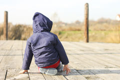 Junge, der auf dem Dock sitzt Stockfotografie