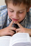 Junge, der auf dem Fußboden erlernt Lizenzfreie Stockbilder