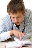 Junge, der auf dem Fußboden erlernt Lizenzfreies Stockfoto