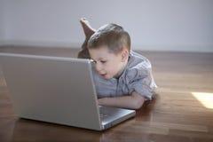 Junge, der auf dem Fußboden mit Laptop-Computer niederlegt Lizenzfreies Stockfoto