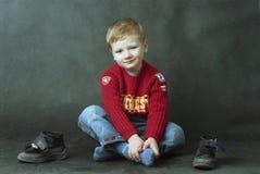 Junge, der auf dem Fußboden sitzt Lizenzfreies Stockbild