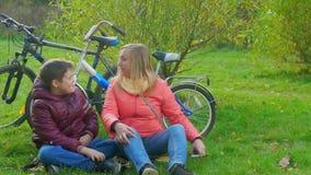 Junge, der auf dem Gras sitzt und Smartphone spielt Mutter nimmt den Smartphone ihres Sohns stock footage