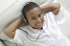 Junge, der auf dem Sofa hört Musik auf obenliegender Ansicht des Kopfhörerporträts liegt Stockfotos