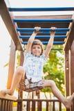 Junge, der auf dem Spielplatz spielt Lizenzfreie Stockfotografie