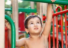 Junge, der auf dem Spielplatz spielt Stockbild