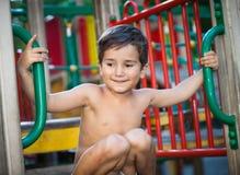 Junge, der auf dem Spielplatz spielt Lizenzfreie Stockbilder