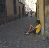 Junge, der auf dem Straßenboden sitzt stockfoto