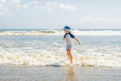 Junge, der auf dem Strand im Wasser spielt lizenzfreie stockbilder