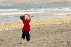 Junge, der auf dem Strand mit einem Frisbee spielt Stockfotografie