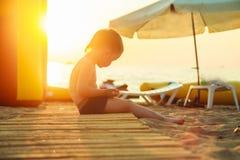 Junge, der auf dem Strand sitzt Lizenzfreie Stockbilder
