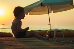 Junge, der auf dem Strand sitzt Lizenzfreies Stockfoto