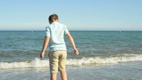Junge, der auf dem Strand spielt stock video