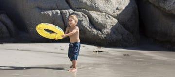 Junge, der auf dem Strand spielt Lizenzfreie Stockbilder