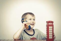 Junge, der auf dem Telefon und der roten Telefonzelle spricht Stockfotos